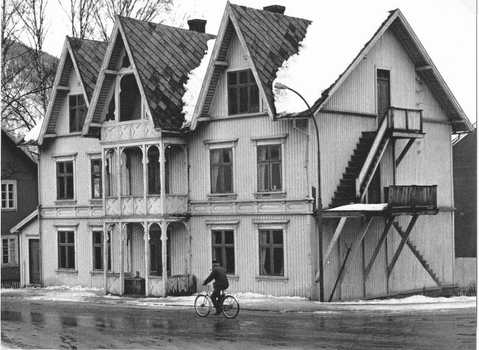 Byggestilen med spisse takutbygg tilsvarte den som var på Otta-hotellene som ble bygd i samme tidsperiode som Nyekren. På veranda og vegg sees utskjæringer som gjør fasaden stilfull etter tiden. Innenfor de to vinduene til venstre var det at Johannes Haugen hadde sitt lensmannskontor.  Bildet er fra slutten av 1950-årene eller først i 1960-årene. Syklisten er Kristian Voldheim, her som vanlig, med sin blå topplue med dusk, og pipe i munnen. Bildet er fra Sel Historielags fotoarkiv.