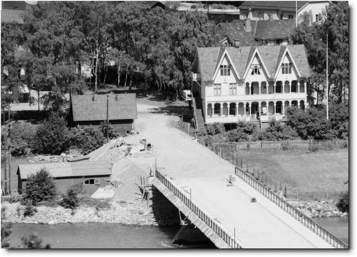 OTTA 1956: Lensmannsgården med Otta kjørebru i forgrunnen. Da huset ble bygd tidlig på 1900-tallet hadde Otta allerede tre hoteller. På denne tiden var det flere sanatorier i dalen, blant annet på Fefor i Fron og Hornsjø i Øyer. En nærliggende tanke er at eieren hadde planer om det samme, å bygge et sanatorium på Otta. På bildet sees en rekke overbygde verandaer. Her kunne nok personer som trengte helsebringende rekreasjon og pleie nyte tilværelsen skjermet under tak, i frisk innlandsluft i et stille og fredfullt landskap med Ottaelva like ved. Bildet er et utsnitt av et prospektkort.
