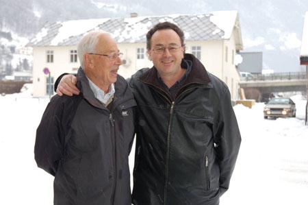 """Per Erling har skrevet artikler, mens Kjell Arne har redigert og publisert. Her er de foran Wangenhuset i Otta sentrum, som er beskrevet i artikkelen """"J.K. Wangen, fra kafé og landhandel til spesialforretning"""". (Foto: Næravisa Norddalen, Otta)"""